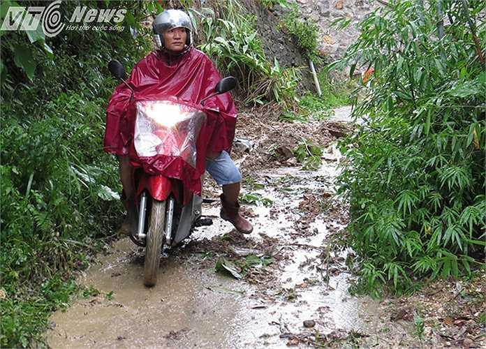 Người dân đi xe máy trên con đường lầy lội, trơn trượt.