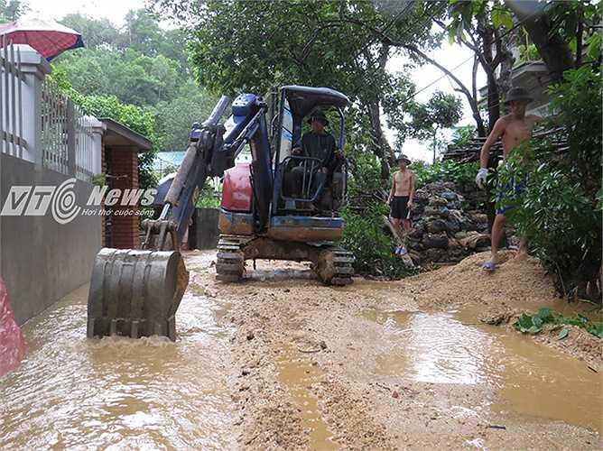 Chiếc máy xúc cùng người dân xúc cát đá, khơi thông dòng chảy trong ngõ chống úng lụt.