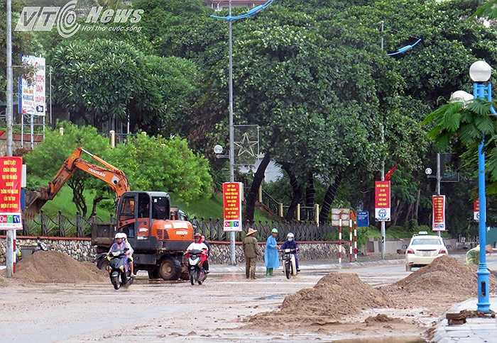 Sáng 29/7, lực lượng chức năng phải huy động lực lượng, phương tiện đến vận chuyển hàng trăm khối đất đá sạt lở xuống đường phố khu vực Bãi Cháy.
