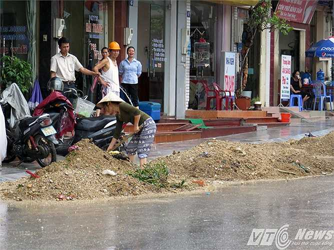 Đất đá từ trên đồi phía sau nhà dân khu vực phường Bãi Cháy đổ đống trước cửa, khiến người dân phải còng lưng dọn dẹp, vận chuyển đi nơi khác.