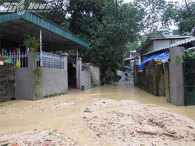 Nước mưa, cát sỏi, bùn đất từ khu vực hiện trường 3 ngôi nhà bị sập, vẫn đổ xuống khu dân cư không ngớt, khiến nhiều nhà dân phía dưới ngõ ngập úng.