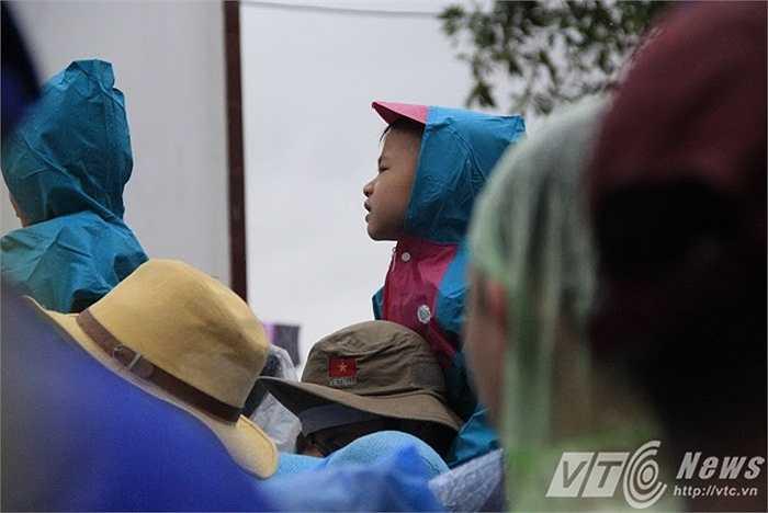 Nhiều em nhỏ đợi tàu với bố mẹ dưới trời mưa, gió lớn.