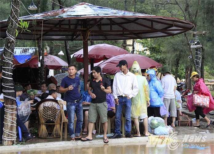 Nhiều du khách buồn rầu đừng đợi tàu tại các nhà hàng gần cảng.