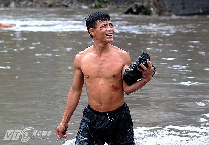 Chú Lam (Người dân phường Mông Dương) cho biết: 'Ngày hôm nay mưa tạnh, nước không chảy xiết chúng tôi mới dám xuống để vớt than.'