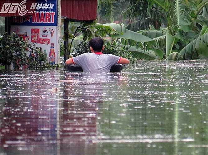 Một người dân bơi về nhà di chuyển đồ đạc còn sót lại.
