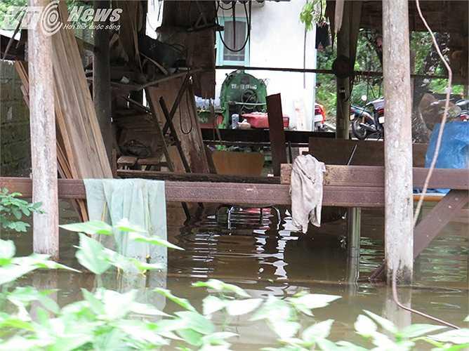 Một xưởng mộc với nhiều đồ gỗ, dụng cụ để 'hành nghề' bị ngập trong nước.