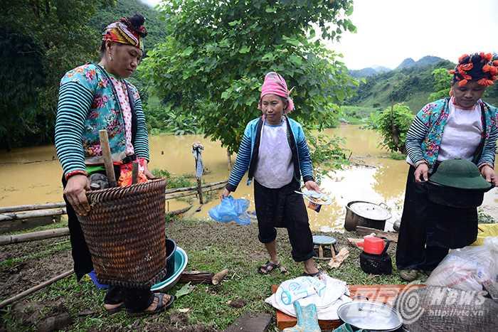 Chị Muồng Thị Dận (36 tuổi) cùng những người phụ nữ khác trong bản đang cố gắng tận dụng chút lương thực, vật dụng vớt lên được sau trận lũ để nấu ăn cho qua ngày.