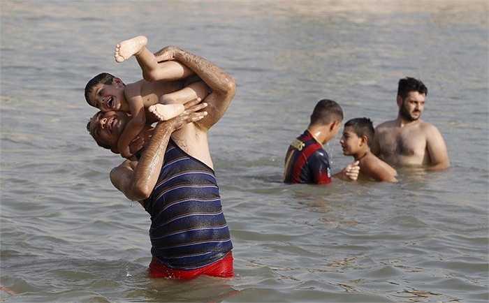 Trẻ em chơi đùa dưới sông Tigris, quận Adhamiya, Baghdad, Iraq