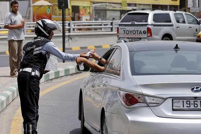 Cảnh sát giao thông phát những chai nước lạnh cho các lái xe ở Amman, Jordan