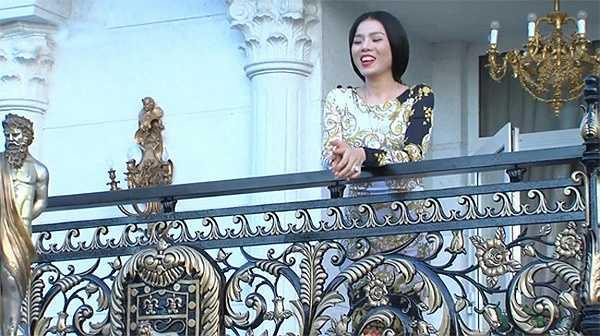 Ca sĩ Lệ Quyên, người cố vấn cho đội của Đàm Vĩnh Hưng, đứng trên ban công trước cửa nhà. Lan can chạm trổ cầu kỳ với nhiều hình ảnh mang lại may mắn cho gia chủ.