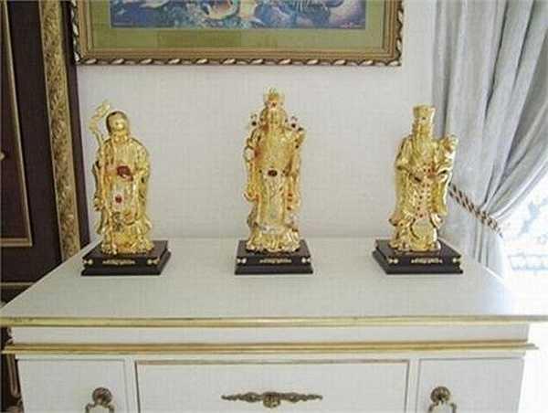 Bộ tượng Phúc - Lộc - Thọ bằng vàng, nạm ngọc được đặt trên mặt tủ cao.