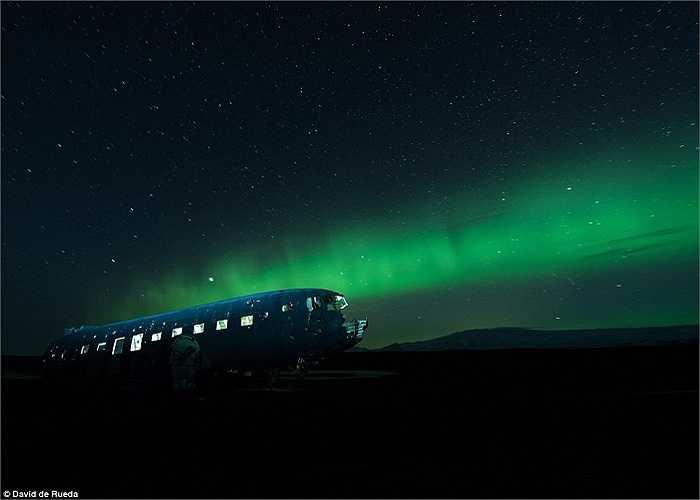 Chiếc máy bay chở khách Douglas DC-3, thông dụng trong thời Thế chiến II, nằm trên bờ biển phía Nam Iceland. Ánh sáng màu xanh do cực quang tạo nên