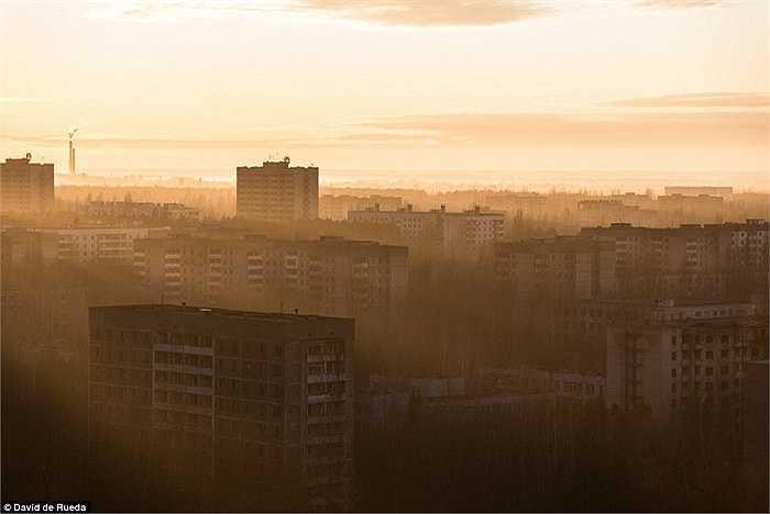 Nhiếp ảnh gia đứng trên tòa nhà Fujiyama cao nhất thị trấn Pripyat để ghi lại cảnh mặt trời mọc ở nơi hoang tàn này