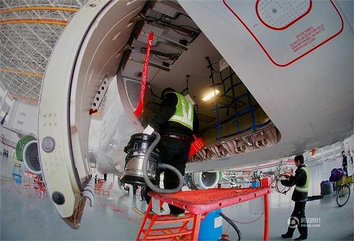 Một nhân viên khác đang dọn vệ sinh máy bay