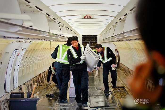 Các nhân viên tháo dỡ phần ghế và phần để hành lý để sửa chữa
