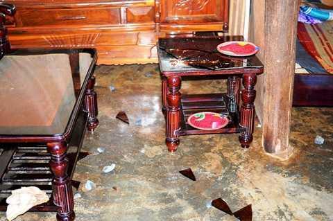 Bàn kính của người dân bị vỡ sau khi đá bay vào nhà - Ảnh: LÂM THIÊN
