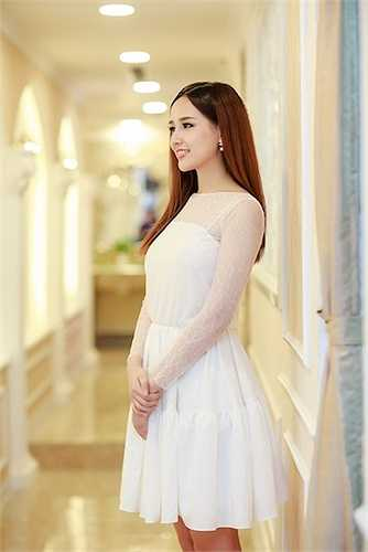 Cô diện một chiếc váy trắng tinh khôi đơn giản.