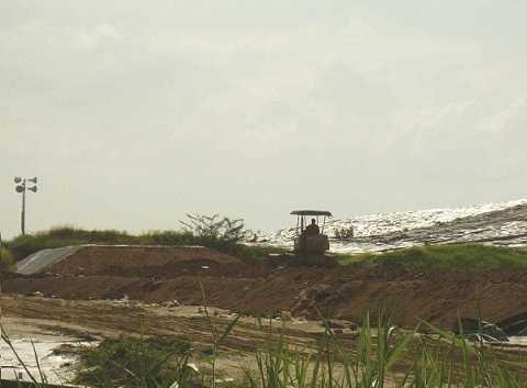 Xe ủi đang san lấp một đoạn bờ đê mới trong kế hoạch mở rộng khu vực chứa rác.