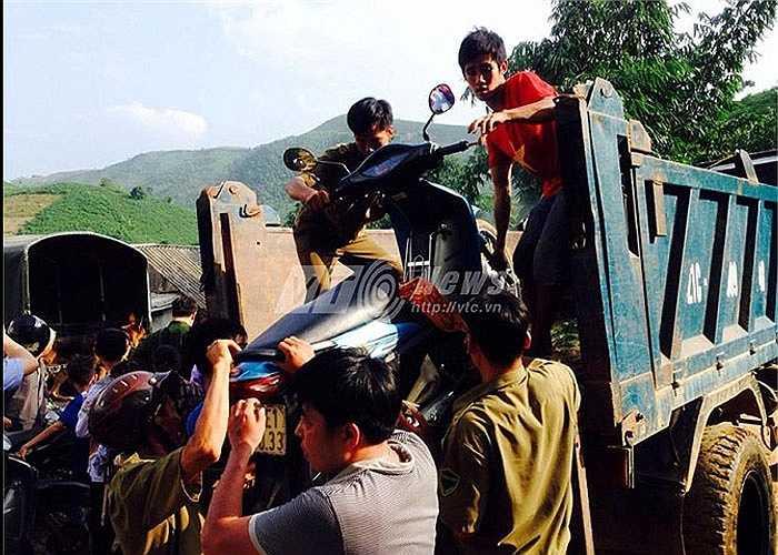 Người dân phải hỗ trợ chuyển xe máy lên xe tải để đi vào hiện trường.
