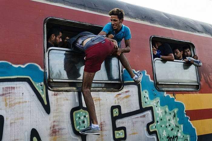 Một người di cư cố tìm cách nhảy vào bên trong con tàu đến biên giới Serbia tại nhà ga Gevgelija