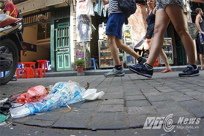 Cô Huyên (Nhân viên một nhà hàng trên phố Tạ Hiện) cho biết: 'Tôi cũng quét liên tục đấy nhưng khách người ta xả ra thì mình cũng chỉ nhắc nhở nhẹ nhàng thôi, chưa kể đường trải đá lồi lõm rất khó quét cho sạch được.'