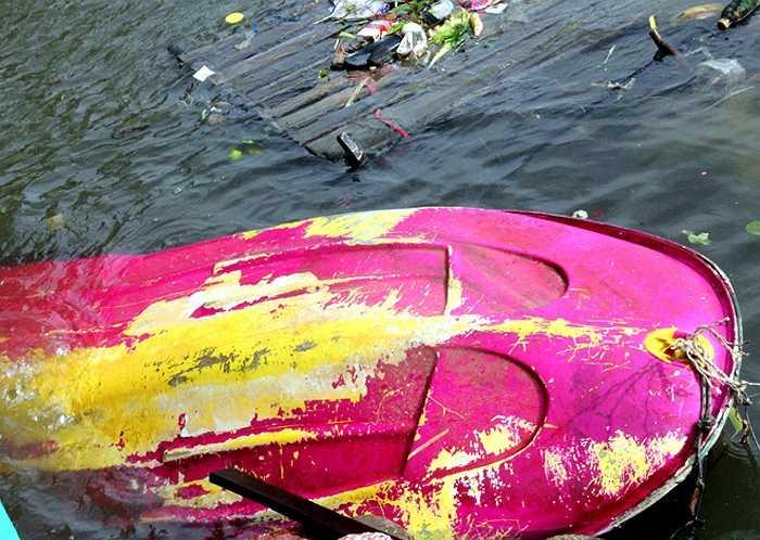 Một chiếc xuồng du lịch bị vứt bỏ tại bãi biển thị trấn Dương Đông, bên cạnh là một bè gỗ 'chở' đầy rác.