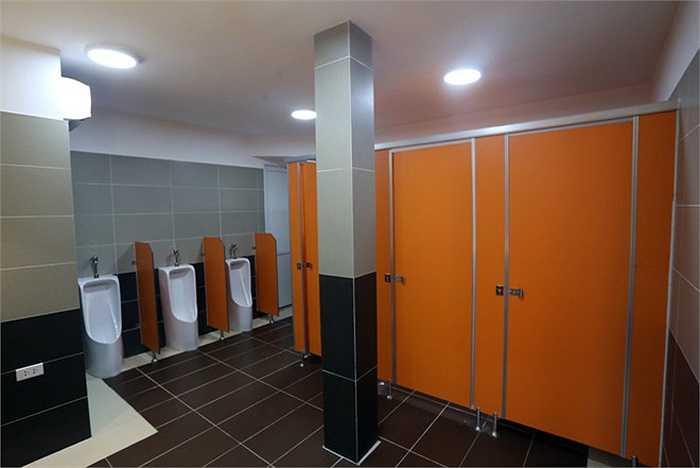 Cửa ngăn nhà vệ sinh này được sơn cùng một màu cam sặc sỡ. Hai nhân viên luôn thay nhau túc trực và dọn dẹp mỗi khi có khách tới sử dụng.