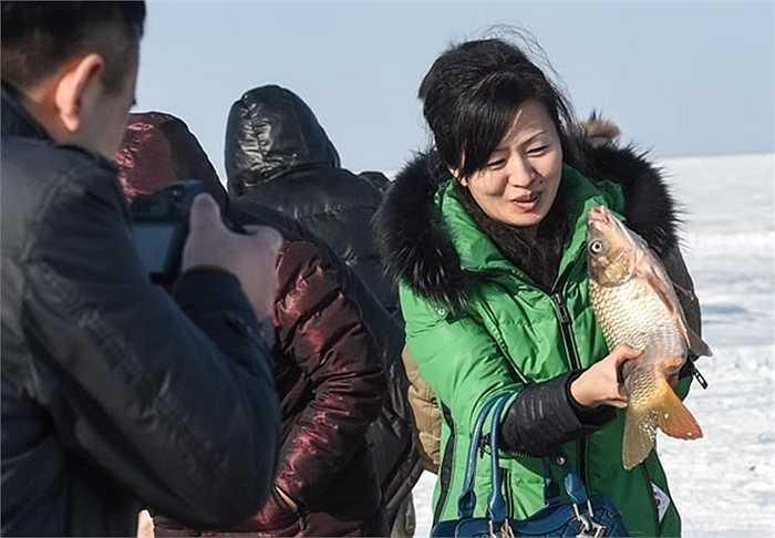 Một du khách thích thú với con cá tươi mới bắt được từ dưới lòng hồ băng
