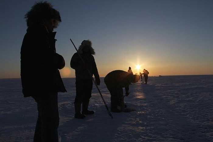 Những ngư dân làm việc bên cạnh các hố băng đào trên mặt hồ