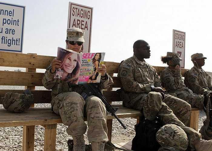Nữ quân nhân thuộc lực lượng đặc nhiệm  Mỹ SSG, tiểu đoàn đặc nhiệm  426 đọc tạp chí trong khi chờ lên trực thăng đến một căn cứ ở Kandahar, miền nam Afghanistan