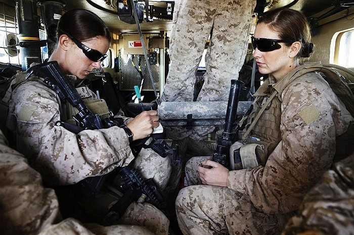 Hai nữ quân nhân Mỹ ngồi trong xe bọc thép trước khi chuẩn bị đi làm nhiệm vụ từ căn cứ ở Musa Quala, tỉnh Helmand, Afghanistan