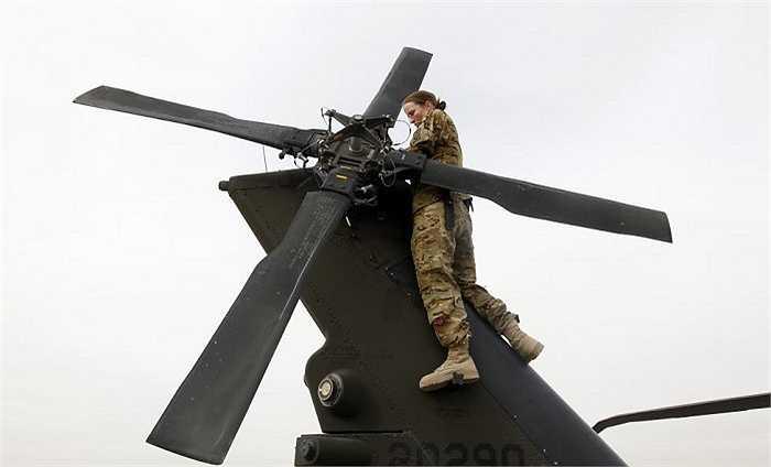 Nữ binh sĩ Mỹ đứng trên chiếc trực thăng kiểm tra hệ thống trong giờ làm việc ở tỉnh Logar, miền đông Afghanistan