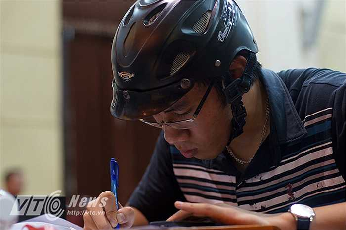 Em Nguyễn Xuân Sơn (18 tuổi), vội vàng đến bàn nộp hồ sơ tới mức quên bỏ mũ bảo hiểm.