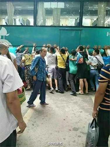 Hàng trăm người qua đường chứng kiến sự việc cùng nhau hợp lực đẩy chiếc xe buýt nghiêng về một bên để cứu bé gái