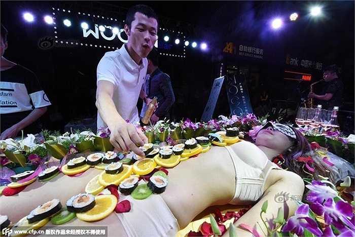 Một khách hàng thưởng thức món ăn bày trên cơ thể người mẫu. Thức ăn gồm có sushi, hoa quả là chanh và kiwi