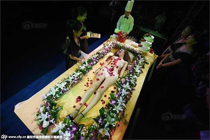 Toàn cảnh người mẫu với cơ thể bày sushi và đồ ăn, hoa quả nhìn từ trên cao