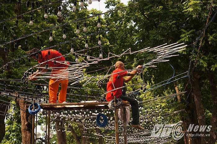 Những người công nhân đang hoàn thiện công việc trang trí dàn đèn 'khủng' trên đường Đinh Tiên Hoàng.