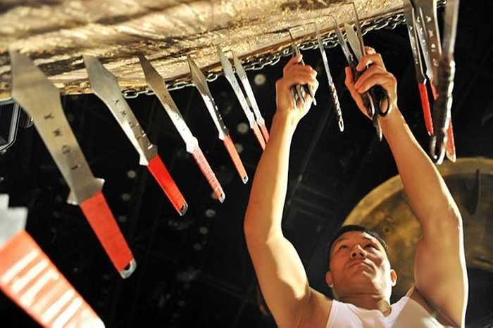 Wang kéo những con dao bị ném vào ván trước khi bắt đầu buổi diễn