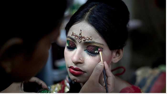 Một người thợ trang điểm cho cô dâu trong ngày cưới