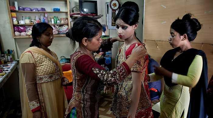 Người thân giúp cô dâu nhí mặc trang phục truyền thống
