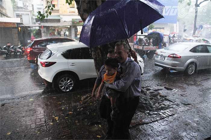 Mặc dù trời mưa rất to nhưng Đại sứ Ted Osius vẫn tươi cười khi đến Chùa Quán Sứ