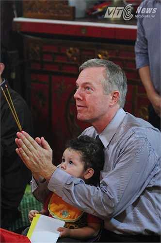 Đại sứ Ted Osius cầm hương ngồi nghe kinh