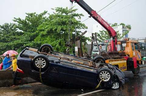 Lực lượng cứu hộ tiến hành cẩu xe Camry - Ảnh: Tấn Lực