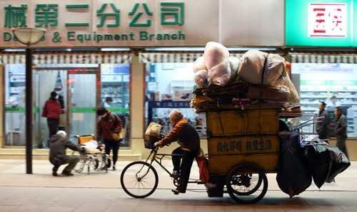 Một người đàn ông đang đạp xe qua một khu phố mua sắm tại Bắc Kinh. Ảnh: Bloomberg
