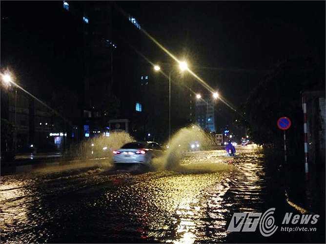 Một xe ôtô tăng ga băng qua đoạn nước ngập trên phố Tôn Thất Thuyết (Nam Từ Liêm, Hà Nội).