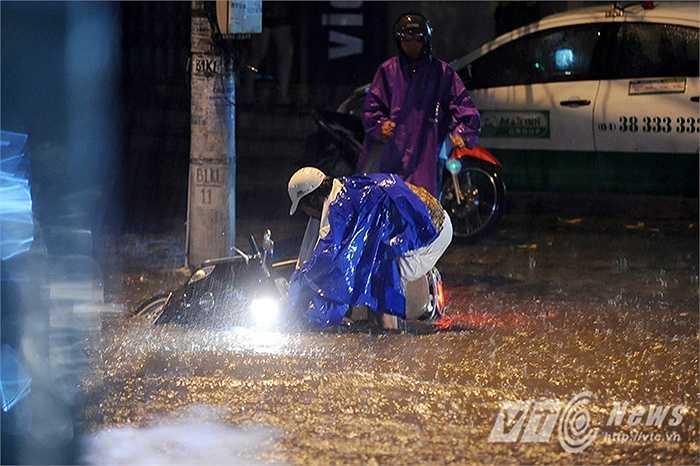 Một người phụ nữ đi xe máy trên phố Lượng Định Của (Đống Đa, Hà Nội) đã bị ngã xe do đâm phải vỉa hè bị nước ngập che mất.