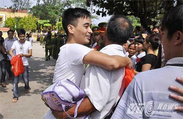 Trong ảnh, người bố tay ôm túi đồ, ôm chầm lấy con trai trong ngày con được đặc xá, trở về với gia đình sau những tháng ngày chấp hành án phạt trong trại giam.