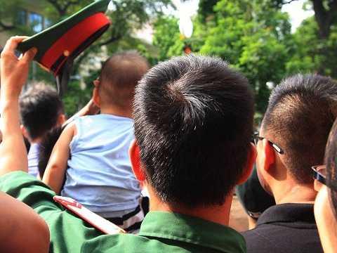 Người lính trẻ âm thầm lấy mũ của mình che cho cháu nhỏ