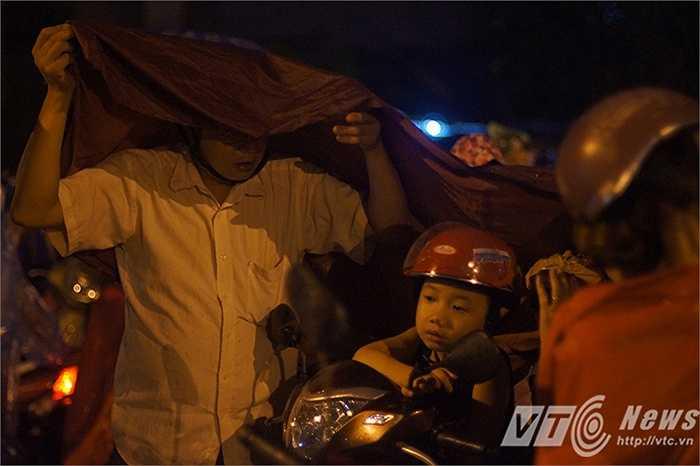 Một ông bố dùng áo mưa che cho con trai mình trong lúc chờ xem pháo hoa