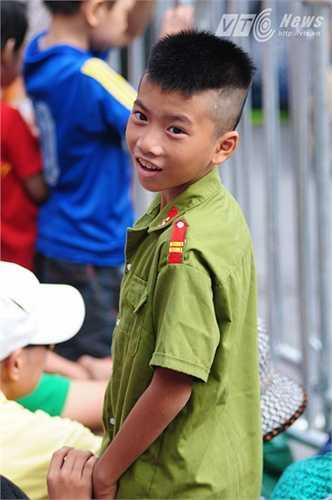 Cậu bé được mặc bộ quần áo công an hồ hởi chờ xem diễu binh (Tùng Đinh/Thực hiện)